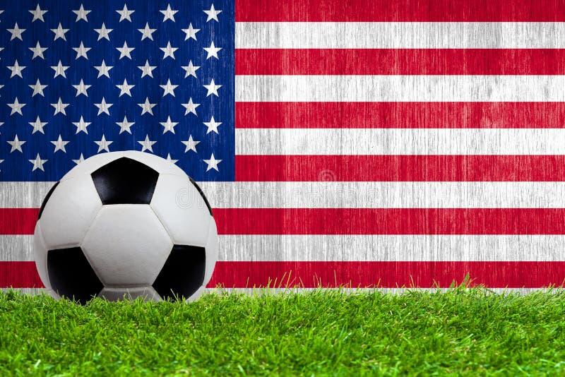 Ballon de football sur l'herbe avec le fond de drapeau des USA photos libres de droits