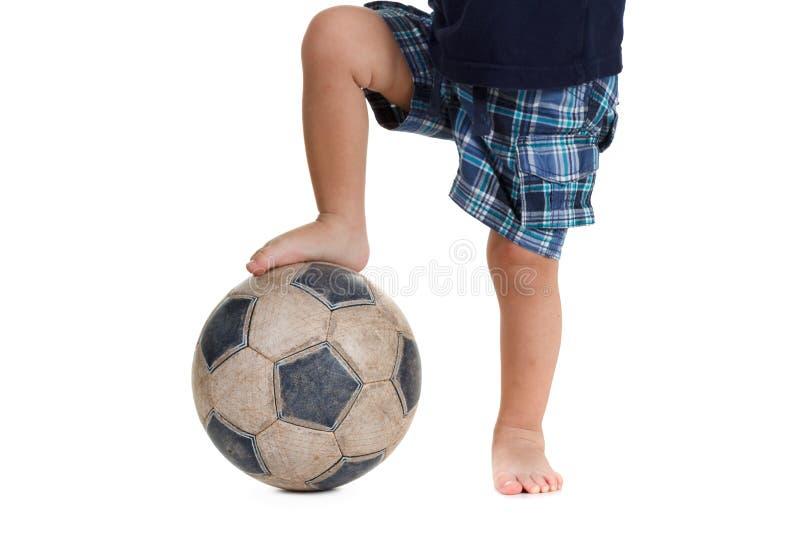 Ballon de football sur le pied d'un joueur de football Blanc d'isolement images stock