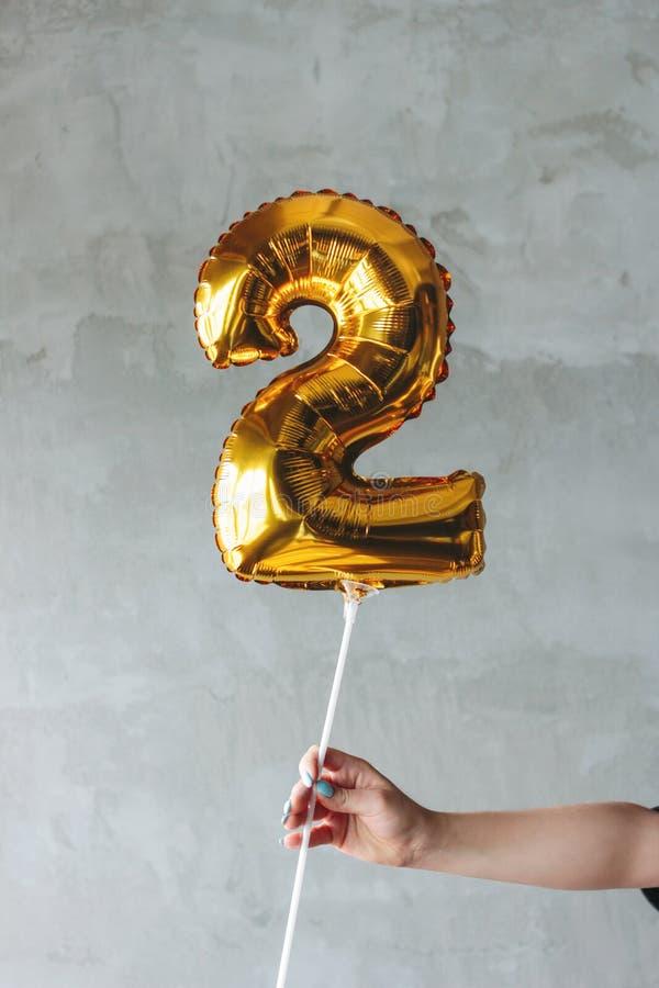 Ballon du numéro deux d'or dans une main femelle sur le fond gris de mur photo libre de droits