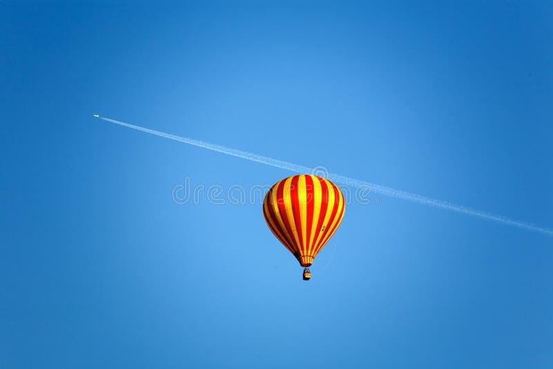Ballon en een vliegtuig met slipstrem op de blauwe hemel stock fotografie