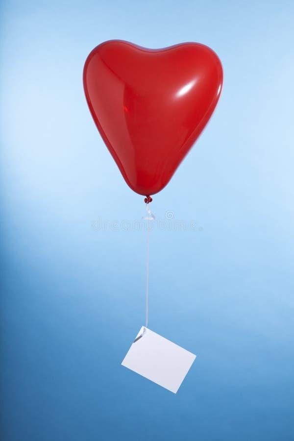 Ballon en forme de coeur avec la carte de voeux vierge photo stock