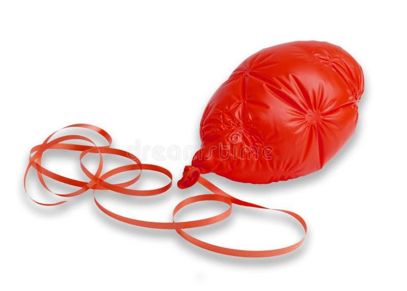 Ballon rouge dégonflé et ruban photographie stock