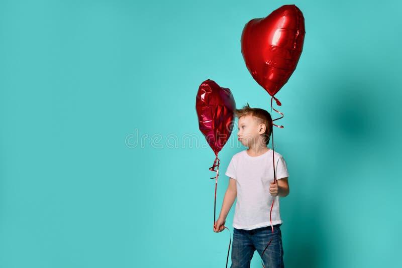 Ballon rouge de coeur de prise d'amour de petit garçon grand pour célébrer le jour de valentines et à le déranger par un autre ba image libre de droits