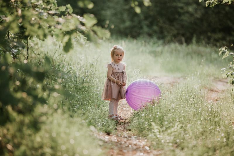 Ballon se tenant an du b?b? 2-5 ?l?gant grand portant la robe rose ? la mode dans le pr? espi?gle photo stock