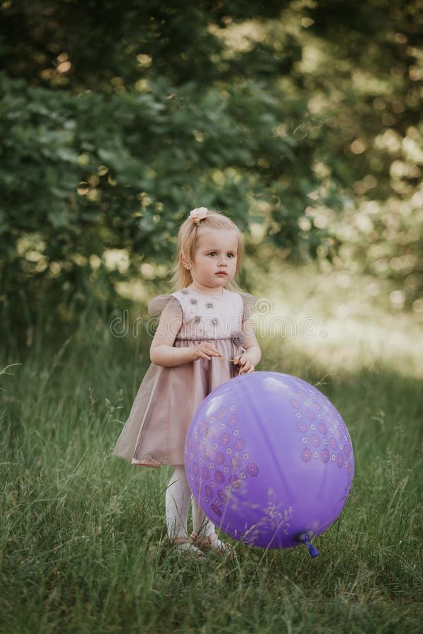Ballon se tenant an du b?b? 2-5 ?l?gant grand portant la robe rose ? la mode dans le pr? espi?gle photographie stock