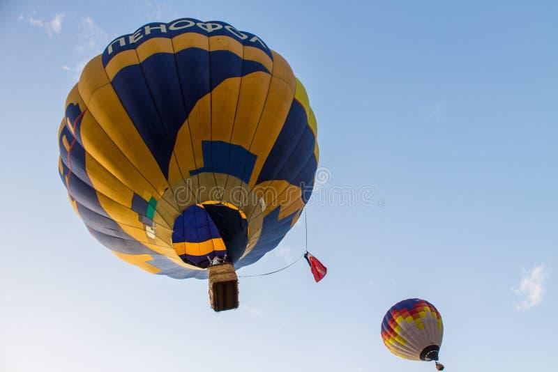Ballon volant avec des passagers dans un panier contre le ciel bleu au festival de la soirée d'été d'aéronautique dans Pereslavl- photo stock