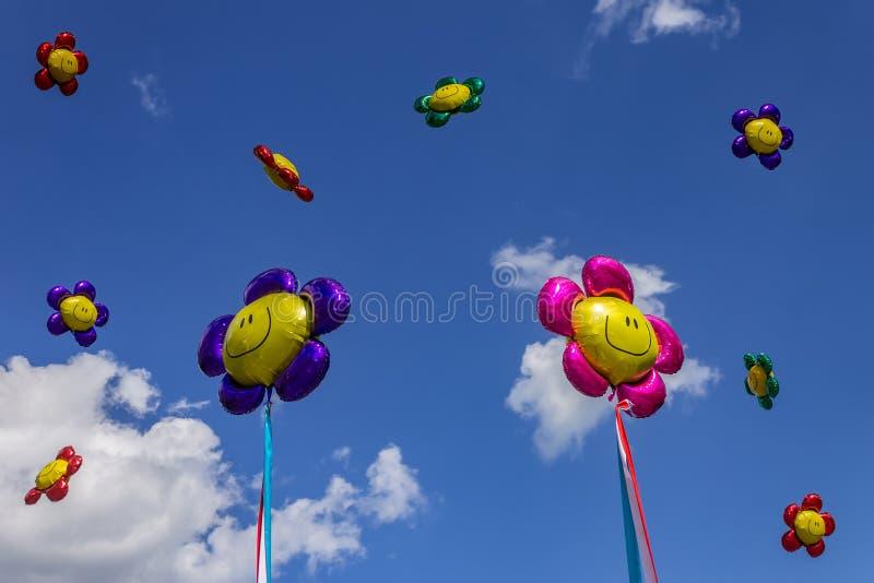 Ballone von verschiedenen Farben im Himmel gegen einen Hintergrund von Wolken stockfotografie