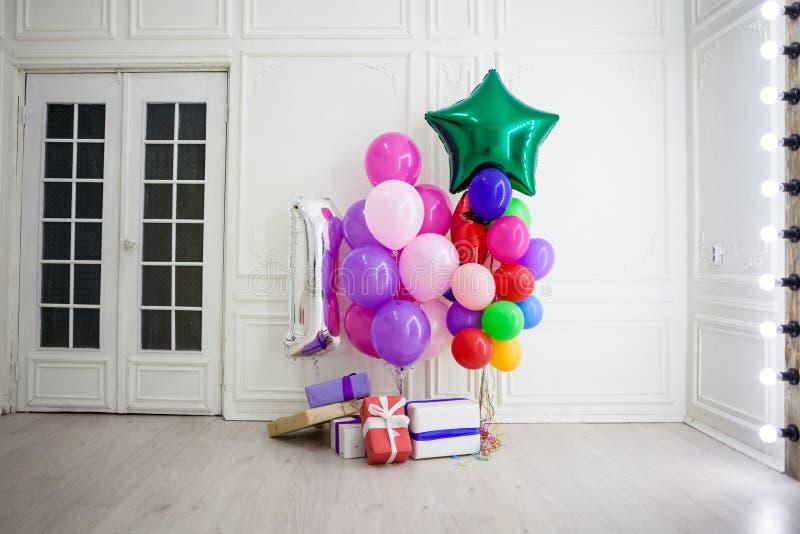 Ballone von verschiedenen Farben mit Geschenken für den Feiertag in einem Raum lizenzfreie stockfotografie