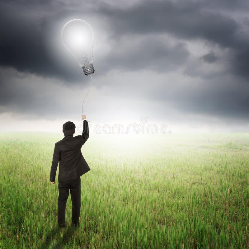 Ballong för kula för affärsman hållande i fält och raincloud arkivfoto
