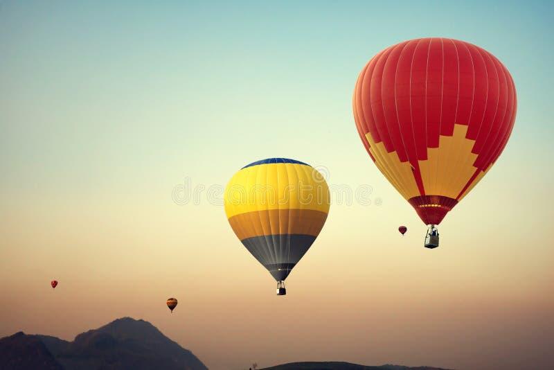 Ballong för varm luft över berget på himmelsolnedgång royaltyfria bilder