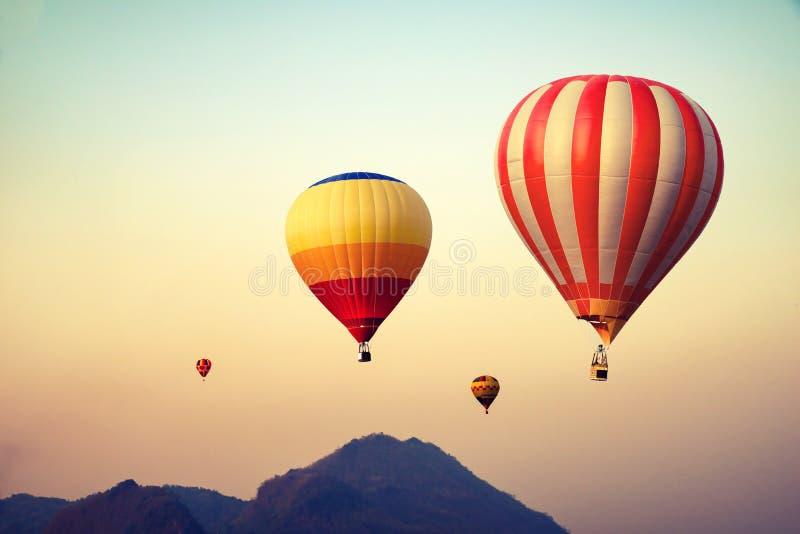 Ballong för varm luft över berget på himmelsolnedgång royaltyfri bild