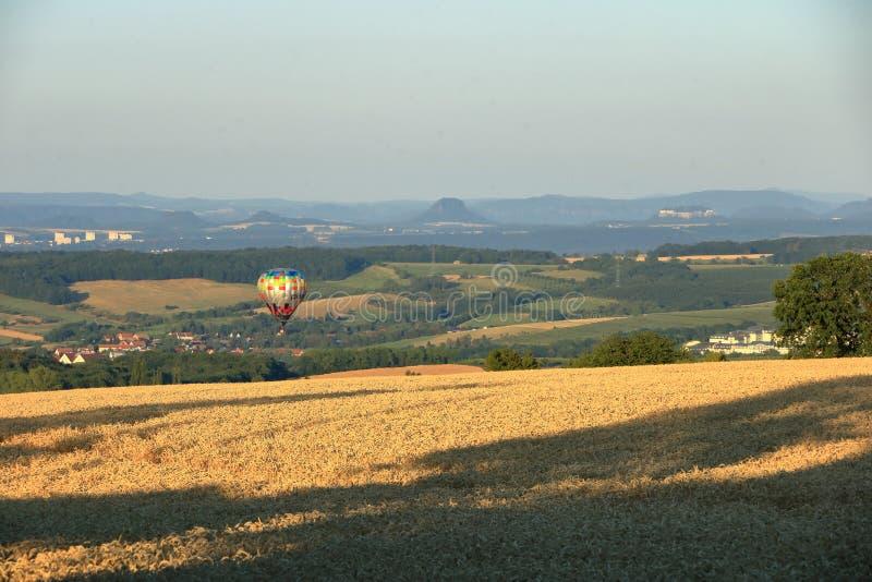 Ballong med varmluft över fältet med blå himmel framför saxony-brytare arkivbilder