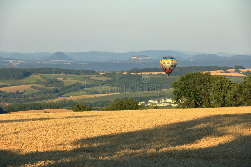 Ballong med varmluft över fältet med blå himmel framför saxony-brytare royaltyfri fotografi