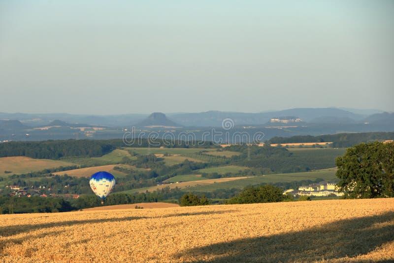 Ballong med varmluft över fältet med blå himmel framför saxony-brytare royaltyfri foto