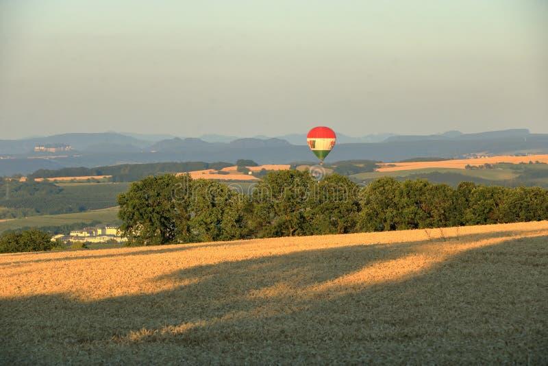 Ballong med varmluft över fältet med blå himmel framför saxony-brytare royaltyfri bild