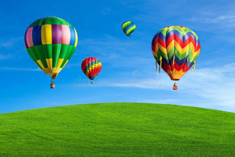 Ballonger för varm luft över grönt fält fotografering för bildbyråer