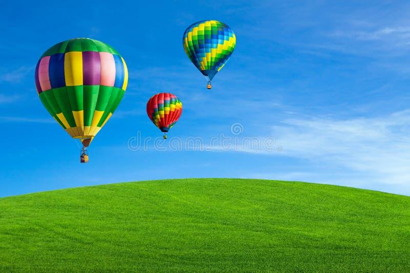 Ballonger för varm luft över grönt fält arkivbild
