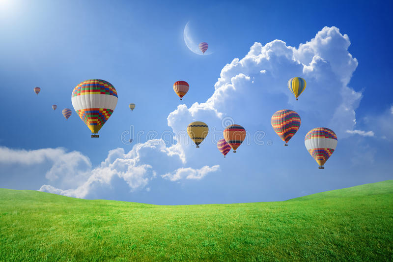 Ballonger för varm luft som flyger i ovannämnt grönt fält för blå himmel arkivbild