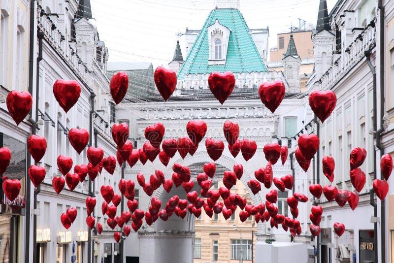 Ballonger i form av röda hjärtor dekorerar gatan för Valen royaltyfria foton