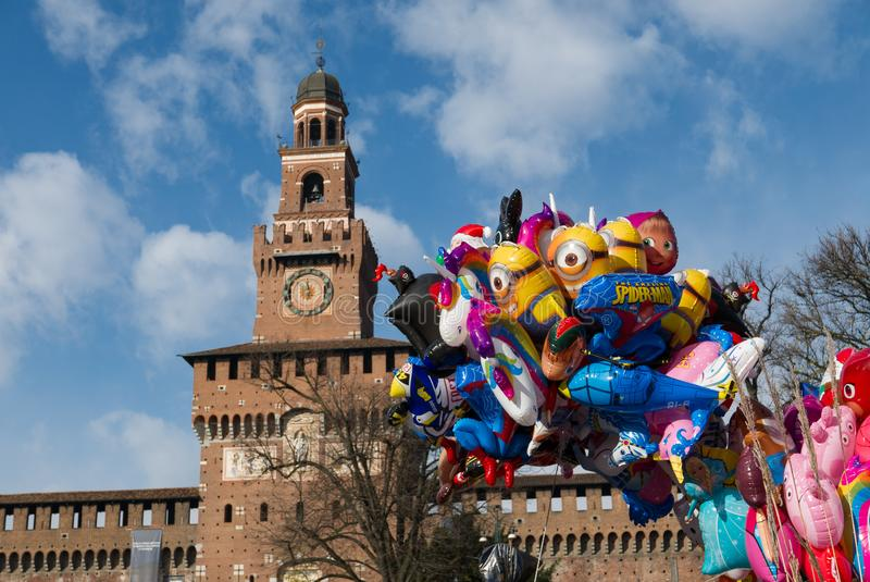 Ballonger i formen av dockor med den Sforzesco slotten i bakgrunden på en solig vinterdag arkivfoto