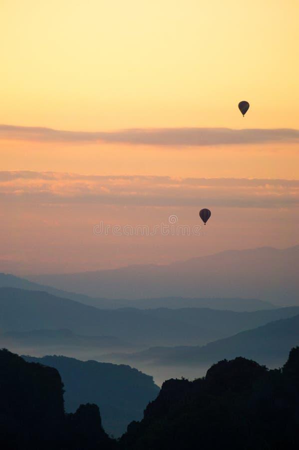 Ballonger som flyger under soluppgång i bergen royaltyfria bilder