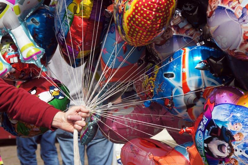 Ballongsäljare som rymmer färgrika ballonger fotografering för bildbyråer