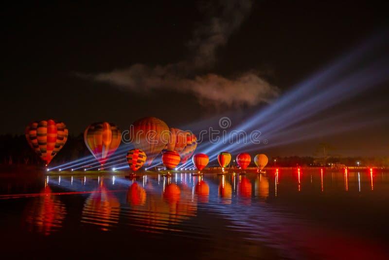 Ballons à air chauds colorés volant au-dessus de la rivière sur le festival de nuit photographie stock