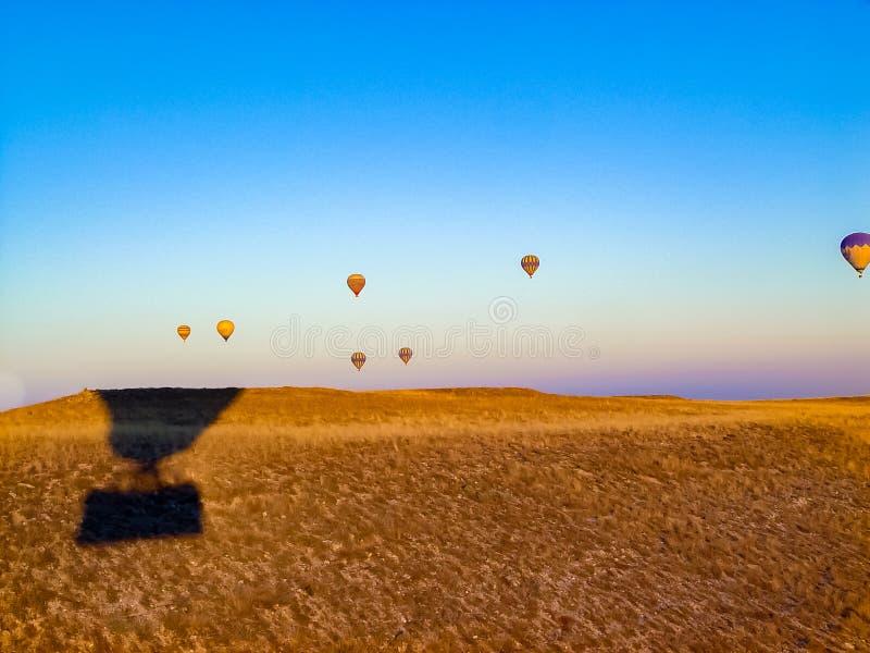 Ballons à air chauds colorés volant au-dessus de la vallée chez Cappadocia photos stock