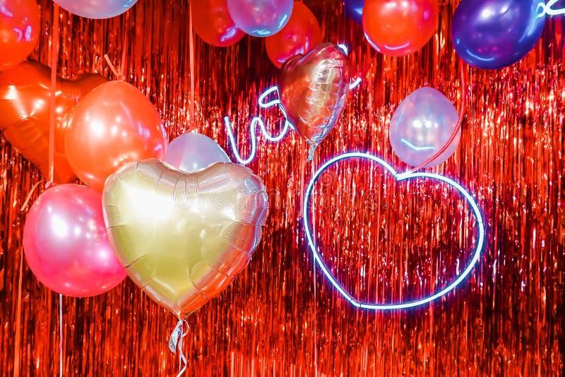 Ballons à air Groupe de ballons en forme de coeur pourpres, roses, bleus colorés d'aluminium avec la lampe au néon de coeur sur l photos libres de droits
