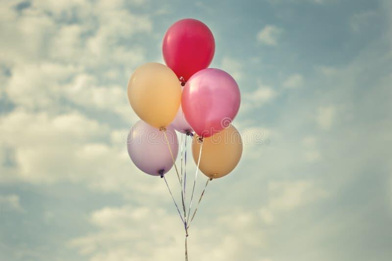 Ballons colorés dans la tonalité de vintage de ciel photographie stock libre de droits