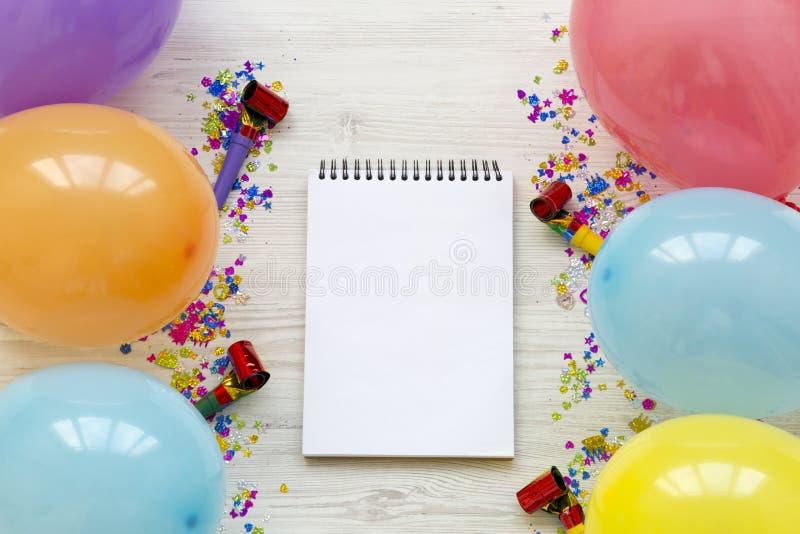 Ballons de diverse partie, confettis et bloc-notes vide Concept de partie de décoration photographie stock