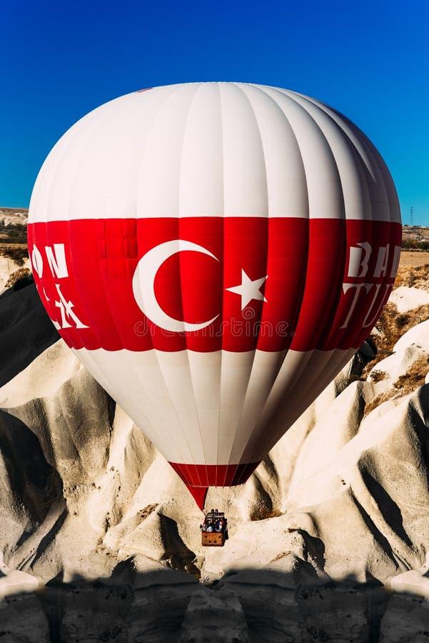 Ballons in de hemel over Cappadocia bij zonsopgang Kleurrijke hete luchtballon die zich omhoog in blauwe hemel beweegt Een eenzam royalty-vrije stock foto's