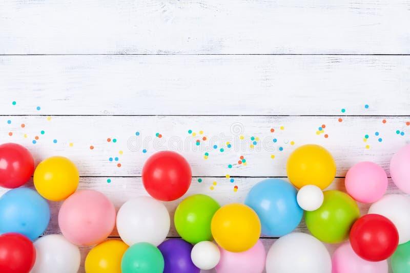 Ballons et confettis color?s sur la vue sup?rieure blanche de table Fond de f?te ou de partie Configuration plate Carte de voeux  photos libres de droits