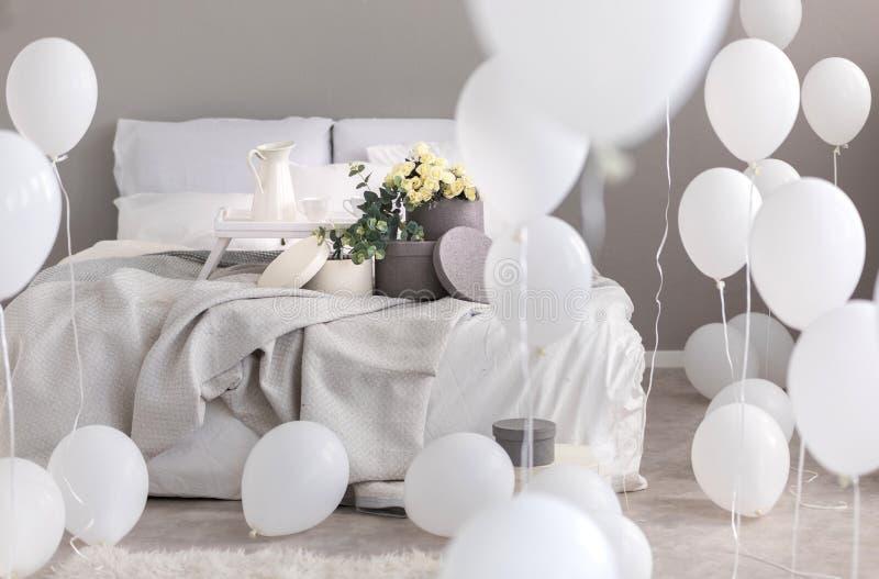Ballons in industriële modieuze slaapkamer met grijs beddegoed, trey en ronde dozen met bloemen op Th-bed royalty-vrije stock foto's