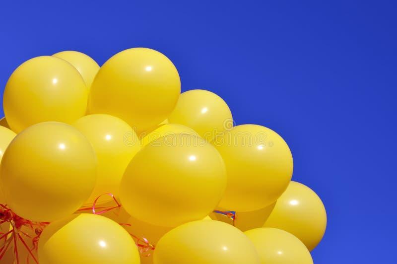 Ballons jaunes sur le fond de ciel bleu images stock