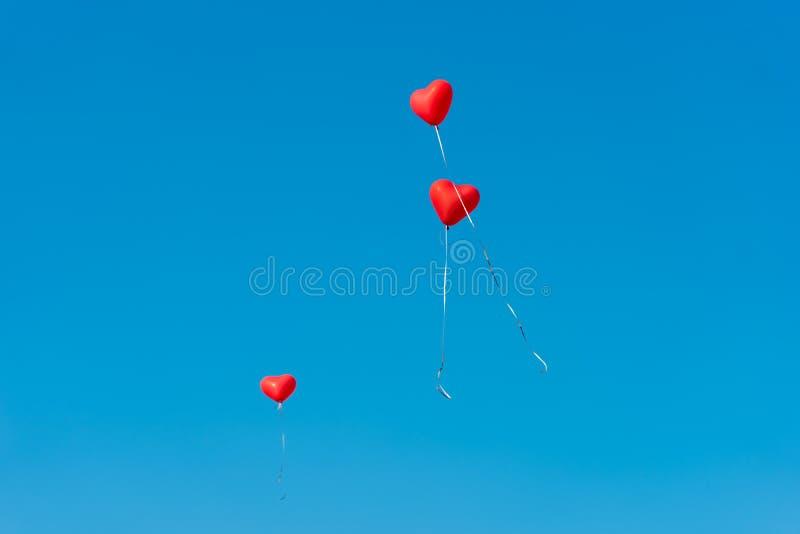 Ballons rouges avec les messages dans le ciel bleu image stock