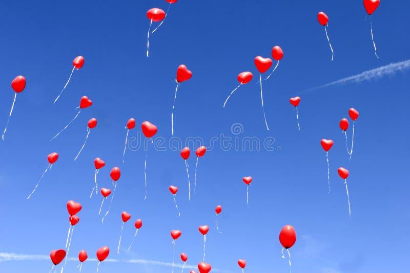 Ballons rouges de coeur dans le ciel images stock