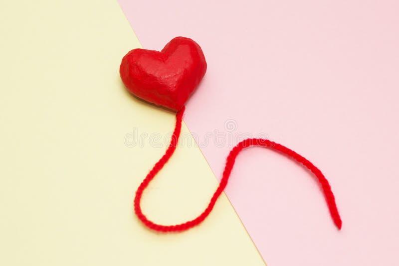 Ballons rouges de coeur sur un jaune et un fond rose photographie stock