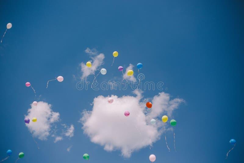 Ballons tegen de blauwe hemel en de wolken Duur vraag en graduatie op school royalty-vrije stock foto