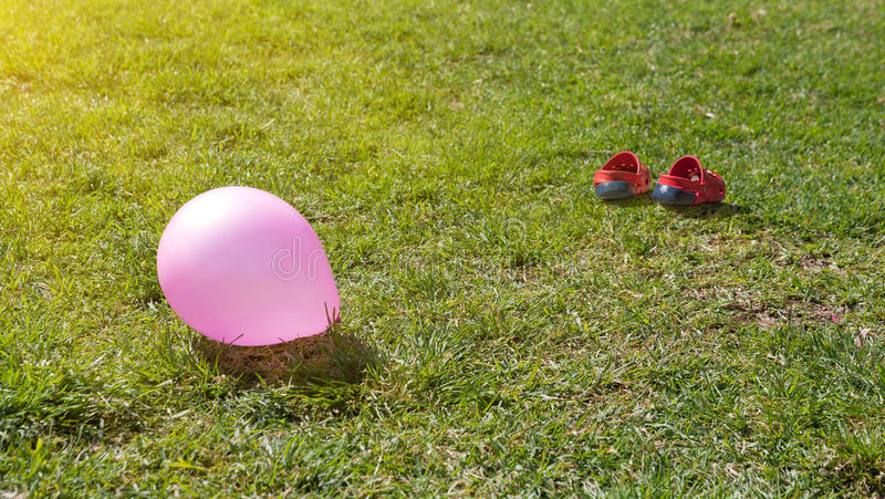 Balloon and children's sandals on green grass royalty free stock image