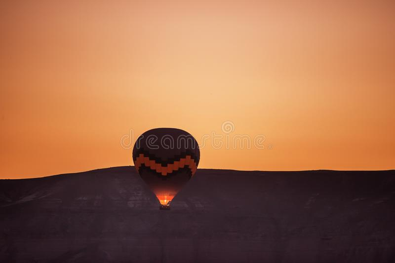 Balloon in flight against the backdrop of the mountain at dawn. stock image