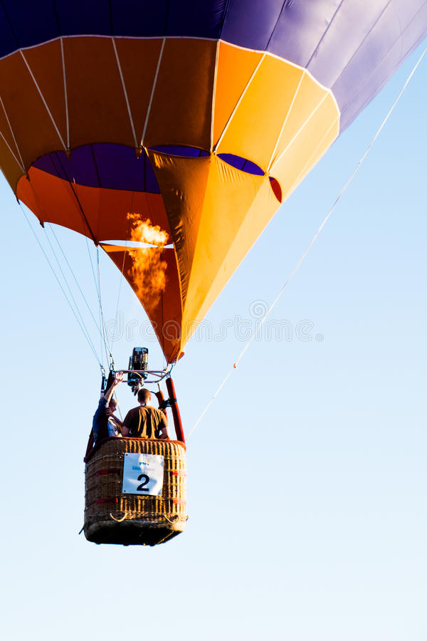 Balloon in flight at festival, Barneveld, Netherlands. Passengers in wicker basket with number flying in hot air balloon festival in Barneveld, Netherlands stock images