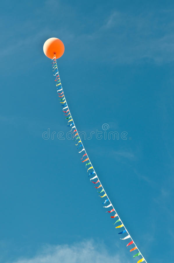 Balloon with Streamers in a Blue Sky royalty free stock photography