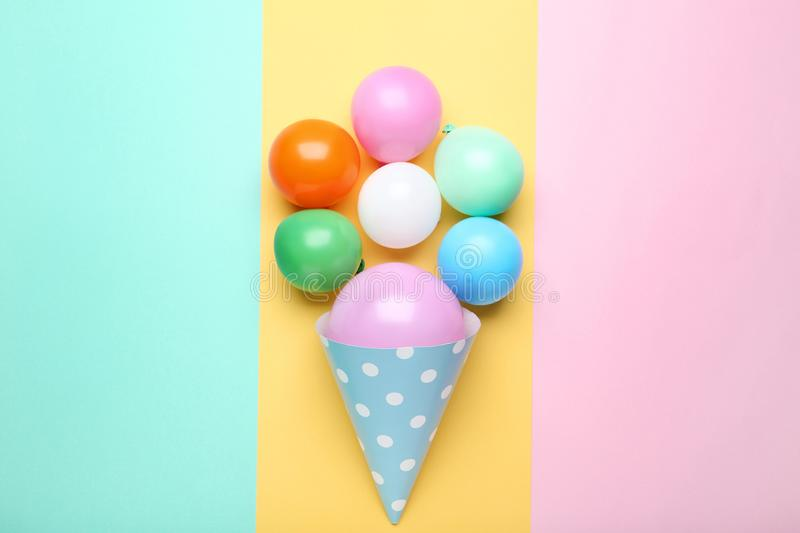 Balloons with birthday paper cap. Rubber balloons with birthday paper cap on colorful background royalty free stock image