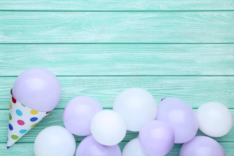 Balloons with birthday paper cap. Rubber balloons with birthday paper cap on wooden table stock photo