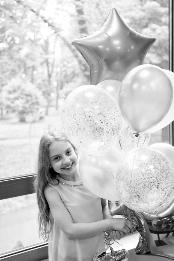 Balloons and birthday tunes. Happy cute little girl celebrating holiday with party balloons. Adorable small child. Smiling with bunch of air balloons. Helium royalty free stock image