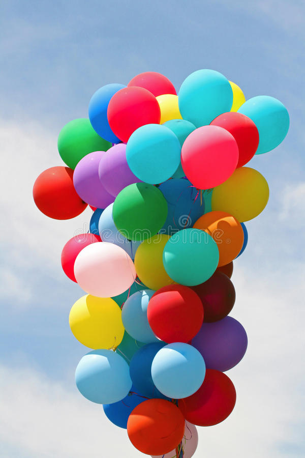 Balloons. Cluster of multiple colored latex balloons floating at parade against blue sky royalty free stock photos