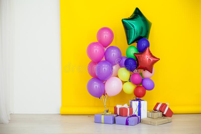 Balloons of different colors with gifts for the holiday stock image