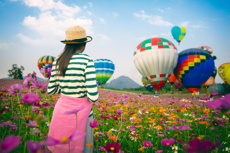 The balloons festival 2017. Young girl looking ballooning at cosmos flowers filed royalty free stock images