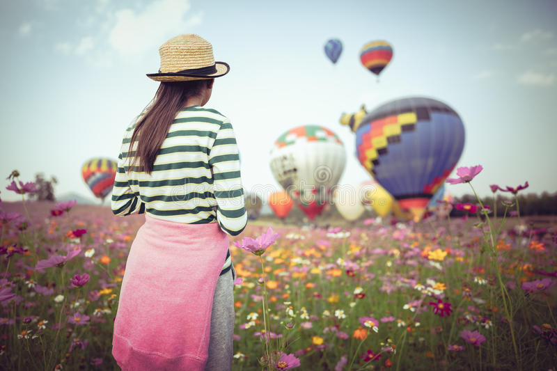 The balloons festival 2017. Young girl looking ballooning at cosmos flowers filed stock image